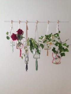 Handknutna amplar som doppats i rosa, grönt, gult och svart. I amplarna hänger glasburkar med pioner, rosor och murgröna.
